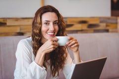 Jolie brune ayant le café utilisant l'ordinateur portable Images stock
