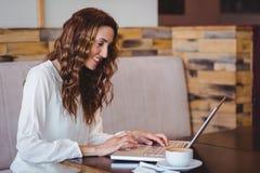Jolie brune ayant le café utilisant l'ordinateur portable Image libre de droits