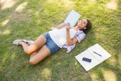 Jolie brune détendant dans l'herbe et le livre de lecture Photo libre de droits