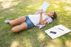 Jolie brune détendant dans l'herbe et le livre de lecture Photo stock