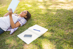 Jolie brune détendant dans l'herbe et le livre de lecture Photographie stock