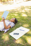 Jolie brune détendant dans l'herbe et le livre de lecture Images libres de droits
