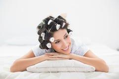 Jolie brune dans des rouleaux de cheveux se trouvant sur son lit Image stock