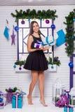 Jolie brune dans une robe noire sur une terrasse blanche avec des cadeaux i Image libre de droits