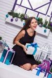 Jolie brune dans une robe noire sur une terrasse blanche avec des cadeaux i Photographie stock