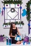 Jolie brune dans une robe noire sur une terrasse blanche avec des cadeaux i Image stock