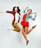 Jolie brune deux et amis blonds d'adolescente sautant le sourire heureux sur le fond blanc, concept de personnes de mode de vie Photo libre de droits