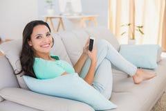 Jolie brune envoyant un texte sur le divan Photos libres de droits