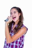 Jolie brune heureuse chantant sur le microphone image libre de droits