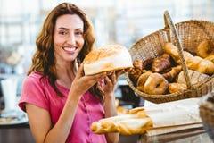 Jolie brune montrant la miche de pain Photographie stock libre de droits