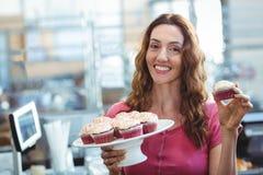 Jolie brune montrant le petit gâteau Photographie stock libre de droits