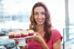 Jolie brune montrant le plat des pâtisseries photos libres de droits