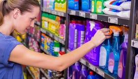 Jolie brune réfléchie regardant le produit dans l'étagère Photographie stock