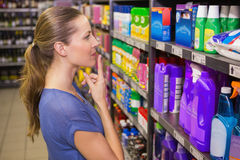 Jolie brune réfléchie regardant le produit dans l'étagère Image stock