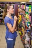 Jolie brune réfléchie regardant le produit dans l'étagère Photo libre de droits