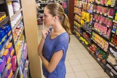 Jolie brune réfléchie regardant le produit dans l'étagère Image libre de droits