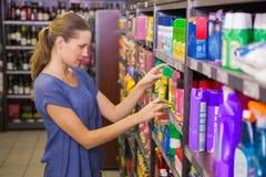 Jolie brune réfléchie regardant le produit dans l'étagère Images libres de droits