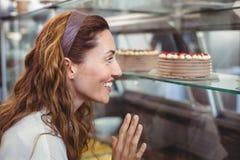Jolie brune regardant des gâteaux par le verre Images stock