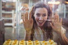 Jolie brune regardant des pâtisseries par le verre Photos stock