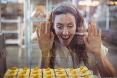 Jolie brune regardant des pâtisseries par le verre Photo stock