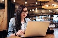 Jolie brune regardant l'écran de son ordinateur portable Images libres de droits