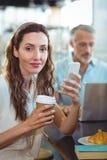 Jolie brune regardant l'appareil-photo avec le smartphone et le café dans des ses mains Images libres de droits