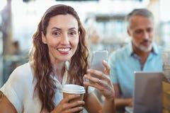 Jolie brune regardant l'appareil-photo avec le smartphone et le café dans des ses mains Photographie stock