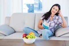 Jolie brune regardant l'appareil-photo et lisant un livre sur le divan Photographie stock libre de droits