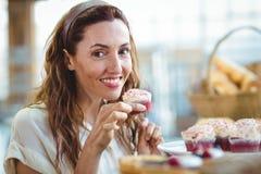 Jolie brune regardant l'appareil-photo et tenant le petit gâteau Images stock