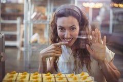 Jolie brune regardant l'appareil-photo par le verre avec le doigt dans la bouche Image stock