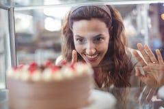 Jolie brune regardant le gâteau de chocolat par le verre Image libre de droits
