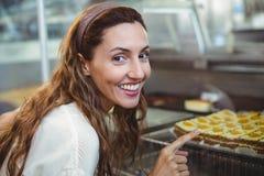 Jolie brune se dirigeant aux pâtisseries par le verre Photos libres de droits