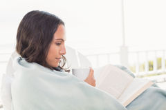 Jolie brune se reposant sur une chaise et lisant un livre Photo libre de droits
