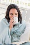 Jolie brune se reposant sur une chaise et un café potable Photographie stock