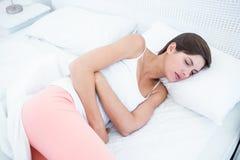 Jolie brune souffrant de la douleur abdominale Photographie stock