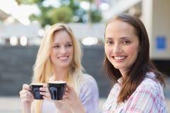 Jolie brune souriant à l'appareil-photo avec l'ami derrière Photos stock