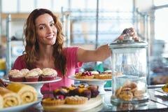 Jolie brune souriant à l'appareil-photo derrière des plats des pâtisseries Images libres de droits