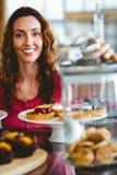 Jolie brune souriant à l'appareil-photo derrière des plats des pâtisseries Photos libres de droits
