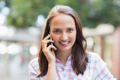 Jolie brune souriant à l'appareil-photo et ayant un appel téléphonique Photo stock