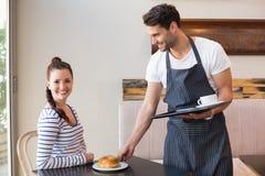 Jolie brune étant servie un bagel Image stock