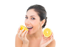 Jolie brune tenant deux moitiés oranges et souriant à l'appareil-photo Photos libres de droits