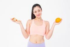 Jolie brune tenant la pizza et l'orange photos stock