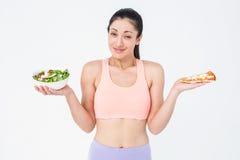 Jolie brune tenant la pizza et la salade image stock
