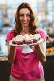 Jolie brune tenant le plat des pâtisseries Image libre de droits