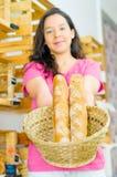 Jolie brune utilisant la chemise rose supportant le panier des baguettes souriant à l'appareil-photo, concept de client de boulan Photos stock