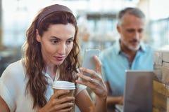Jolie brune utilisant son smartphone avec du café dans sa main Photos stock