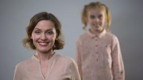 Jolie caméra de sourire de jeune dame avec la fille blonde se tenant derrière, connexion banque de vidéos