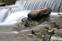 Jolie cascade sur des pierres de roche Images stock