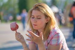Jolie consommation de jeune femme et pomme de caramel rouge ac?r?e en parc pendant le jour ensoleill? photo stock