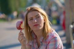 Jolie consommation de jeune femme et pomme de caramel rouge ac?r?e en parc pendant le jour ensoleill? image stock